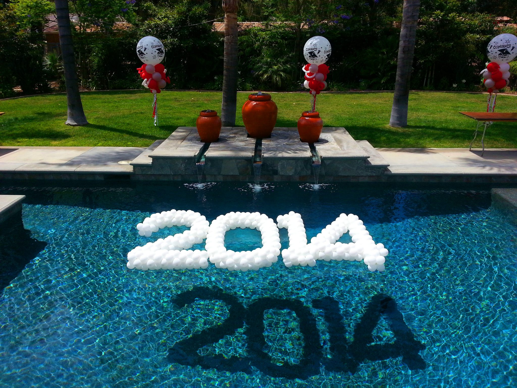Balloon sculpture 2014 grad floating in pool balloons for Pool decorations